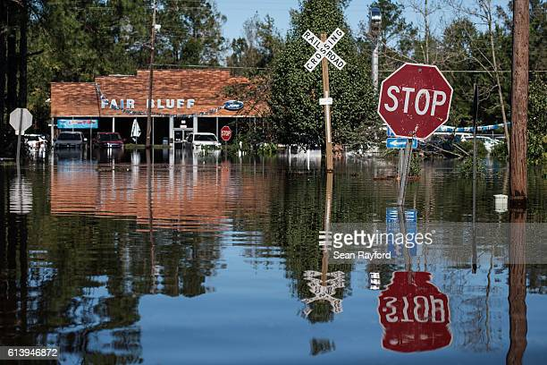 A roadway is flooded by remnants of Hurricane Matthew on October 11 2016 in Fair Bluff North Carolina Thousands of homes have been damaged in North...