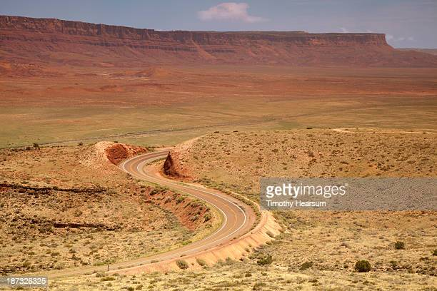 roadway through desert, vermillion cliffs beyond - vermilion cliffs stock pictures, royalty-free photos & images