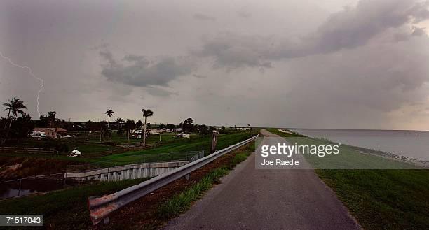 A roadway winds along the rim of the Herbert Hoover Dike for 140 miles encircling Lake Okeechobee July 25 2006 near Pahokee Florida The dike has been...