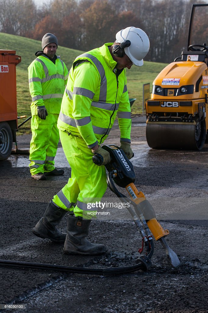 Roadworker using pneumatic drill or Jack Hammer. : Stock Photo