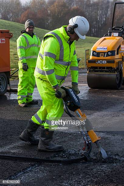 Roadworker using pneumatic drill or Jack Hammer.