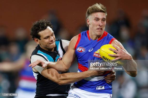 Roarke Smith of the Bulldogs is tackled by Steven Motlop of the Power during the 2021 AFL Second Preliminary Final match between the Port Adelaide...