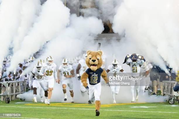Roary the Panther, mascot with the FIU Golden Panthers leads members of the team on to the field prior to their game against the Arkansas State Red...