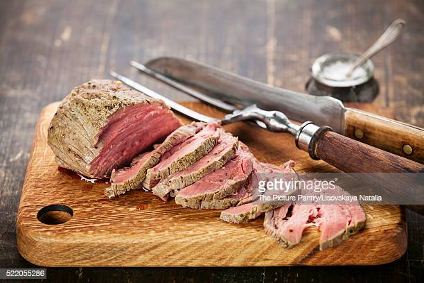 Roast beef on cutting board with saltcellar and meat fork
