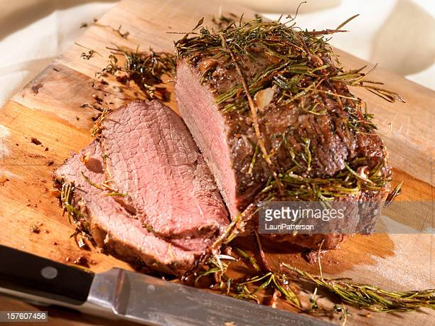 Roast Beef with Rosemary on a Cutting Board