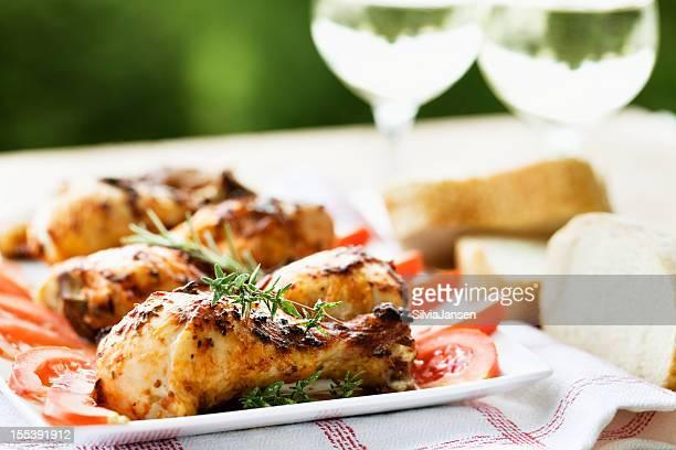 Pollo asado las piernas y vino blanco en un picnic