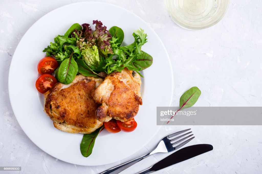 Roast chicken  legs on white plate over light gray plaster texture table : Stock Photo