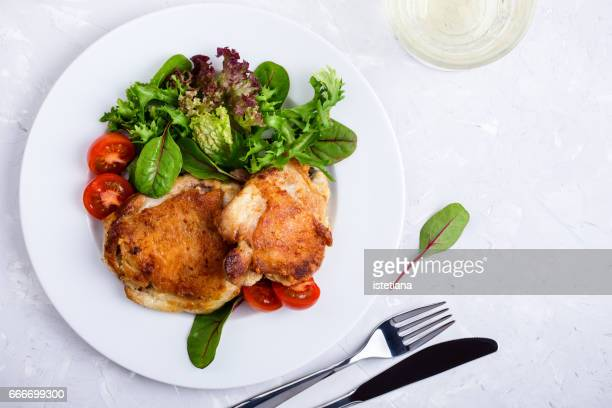 Roast chicken  legs on white plate over light gray plaster texture table
