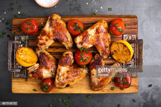 Roast chicken wings on cutting board served with lemon and tomatoes