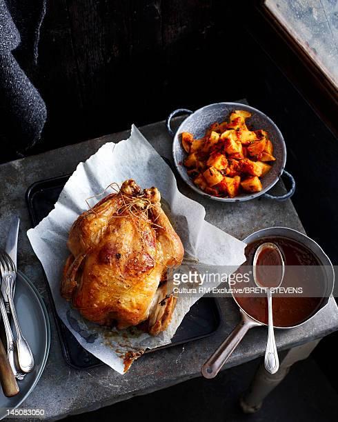 Roast chicken with bowl of gravy