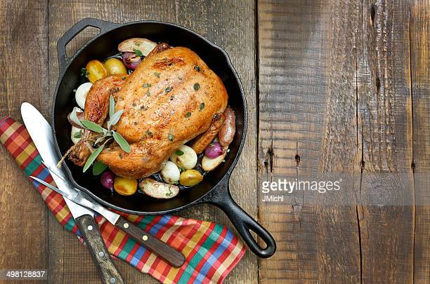 Roast Chicken with Potatoes and Onions in Cast Iron Pan.