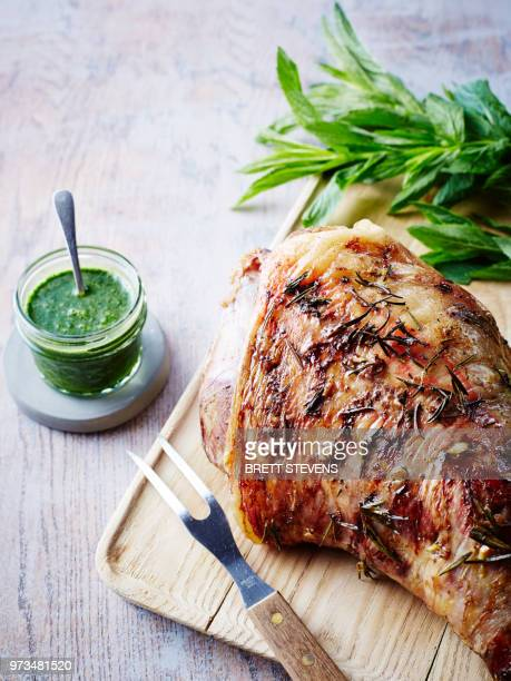 roast leg of lamb on chopping board with jar of mint sauce, close-up - leg of lamb stock pictures, royalty-free photos & images
