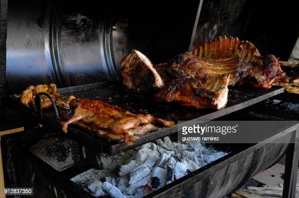 roast pork and chicken on charcoal grill