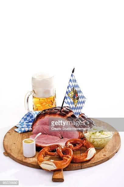 Roast pork, pretzels and mug of beer on wooden board, close-up