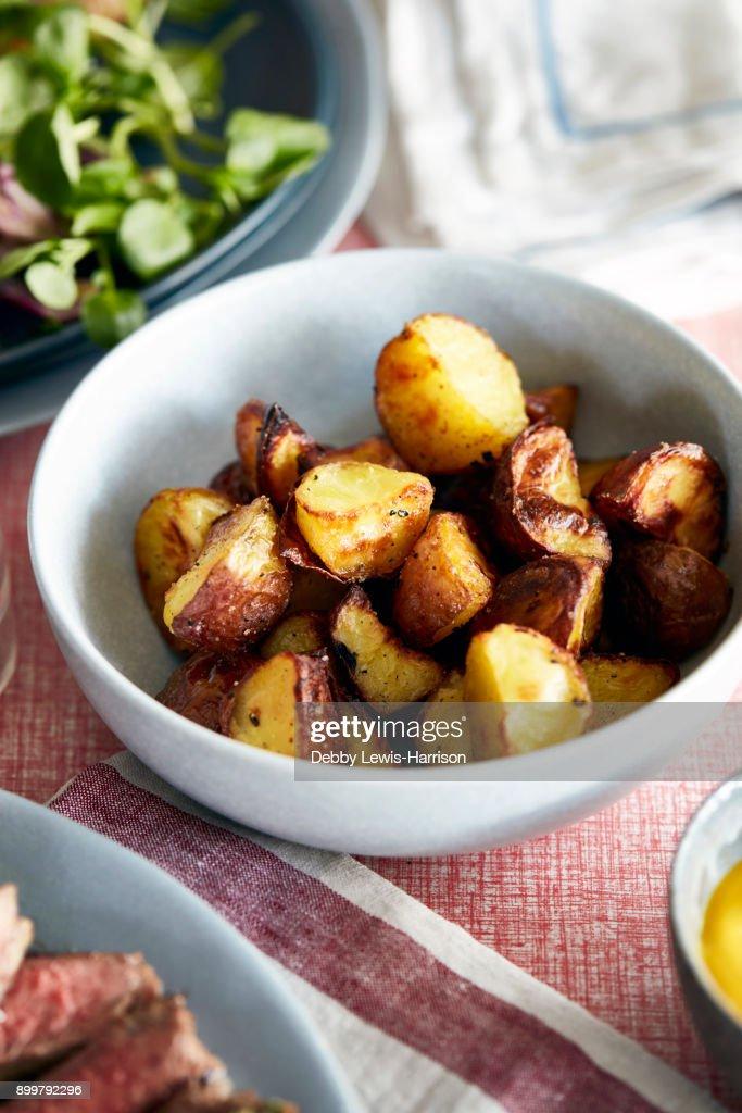 Roast potatoes in bowl, close-up : Stock Photo