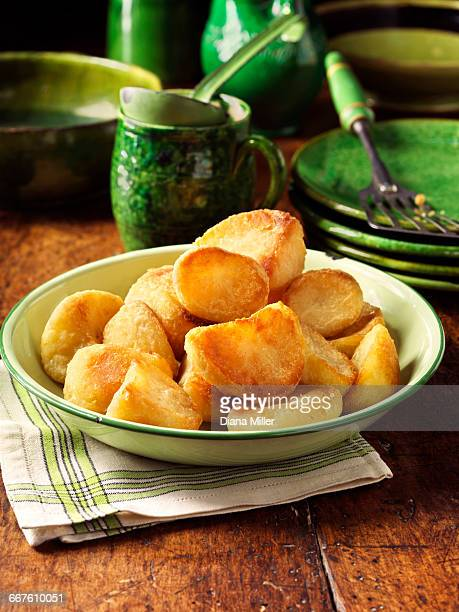 roast potatoes in vintage green bowl, plates and fork, rustic wooden table - ローストポテト ストックフォトと画像