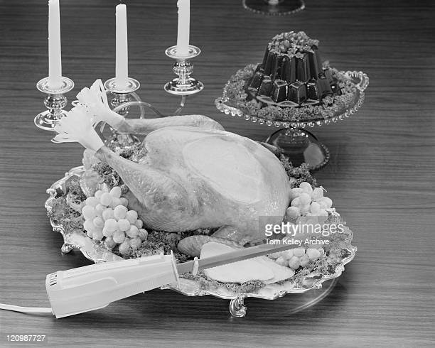 Roast turkey garnished with grapes, jelly and candle stand beside it