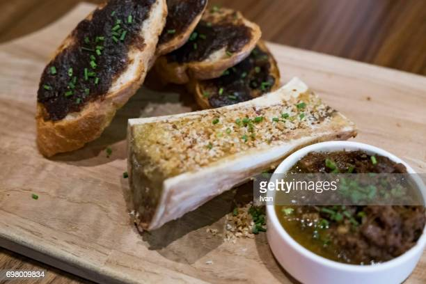 Roasted Beef Bone Marrow with Sliced Baguette and Caramelized Onions