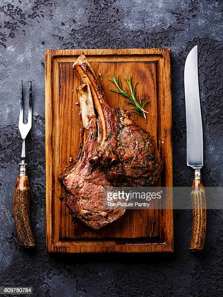 roasted beef ribs on bone on wooden cutting board with knife and fork carving set on dark background - carving knife stock pictures, royalty-free photos & images