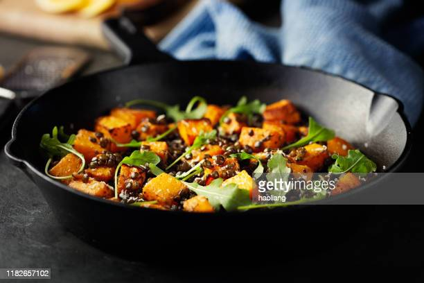 roasted butternut squash with green lentils and rocket leaves - lentil stock pictures, royalty-free photos & images