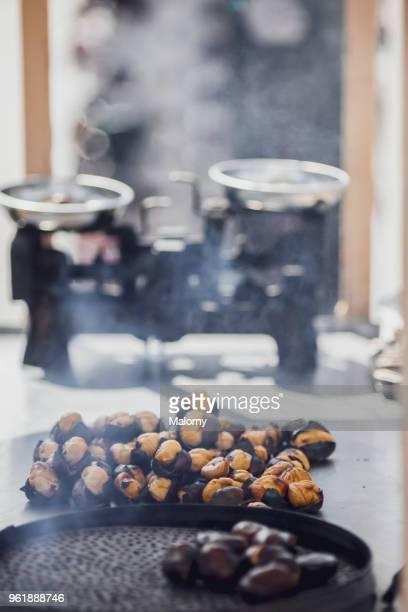 roasted chestnuts in pan with scale in the background. - kastanie laubbaum stock-fotos und bilder