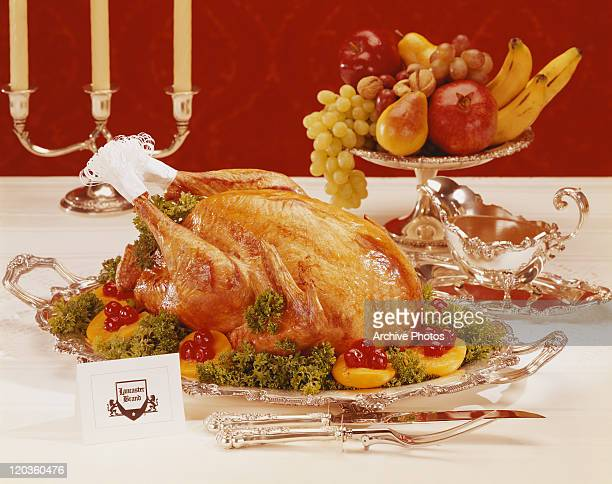 Roasted chicken and fruits in silver crockery