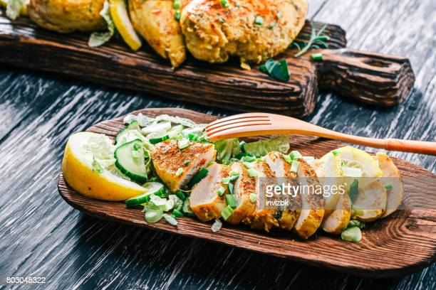 Roasted chicken breast on rustic wood