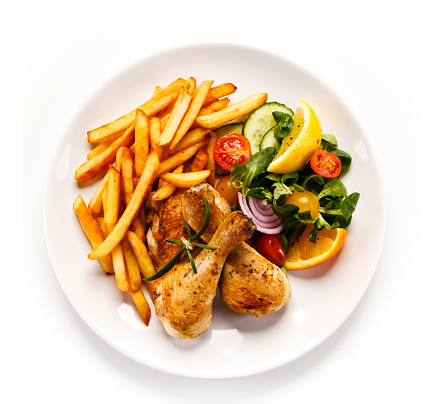 Roasted chicken drumsticks, French fries and vegetables 1079751040