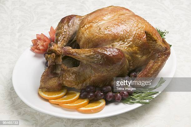 A roasted chicken on a plate with garnishes