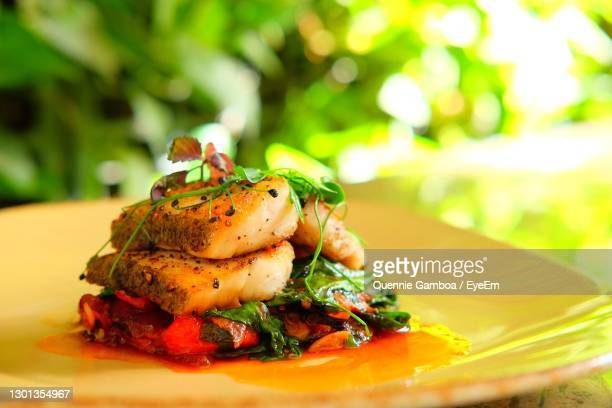 roasted cod with a roasted bell pepper stew, garlic , and spinach - greater manila area stock-fotos und bilder