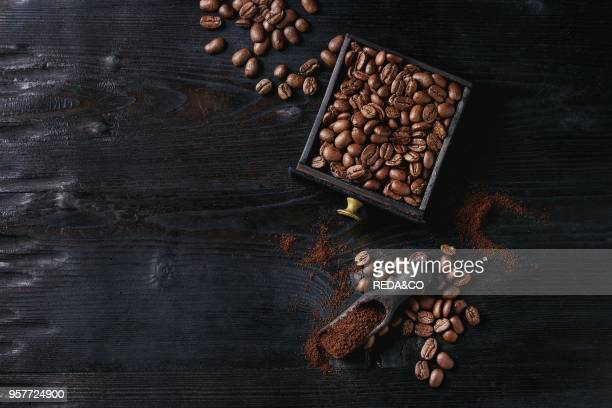 Roasted coffee beans and grind coffee in wood box with scoop over black wooden burnt background Top view with space