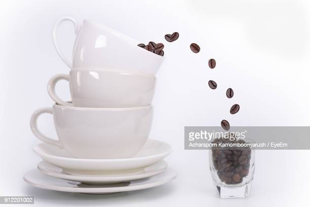 Roasted Coffee Beans Falling In Glass From Cup Over White Background