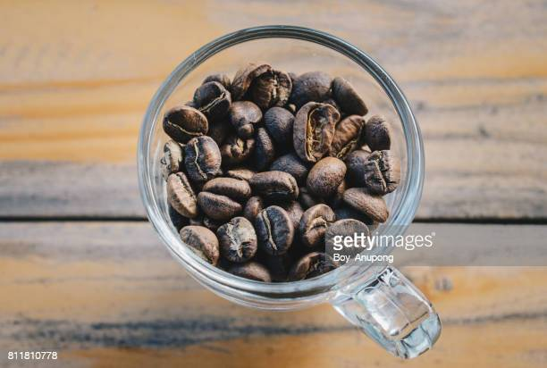 Roasted coffee beans in a cup placed on the wooden table.