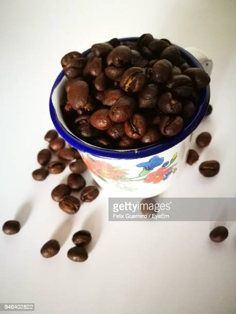 Roasted Coffee Beans In Cup On Table