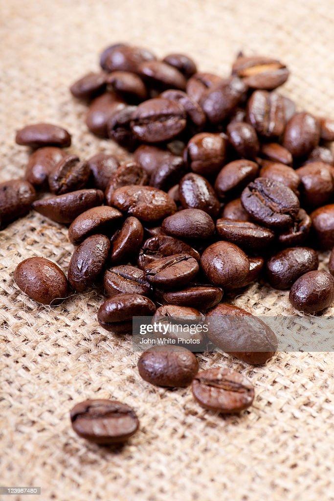 Roasted coffee beans on hessian bag : Stock Photo