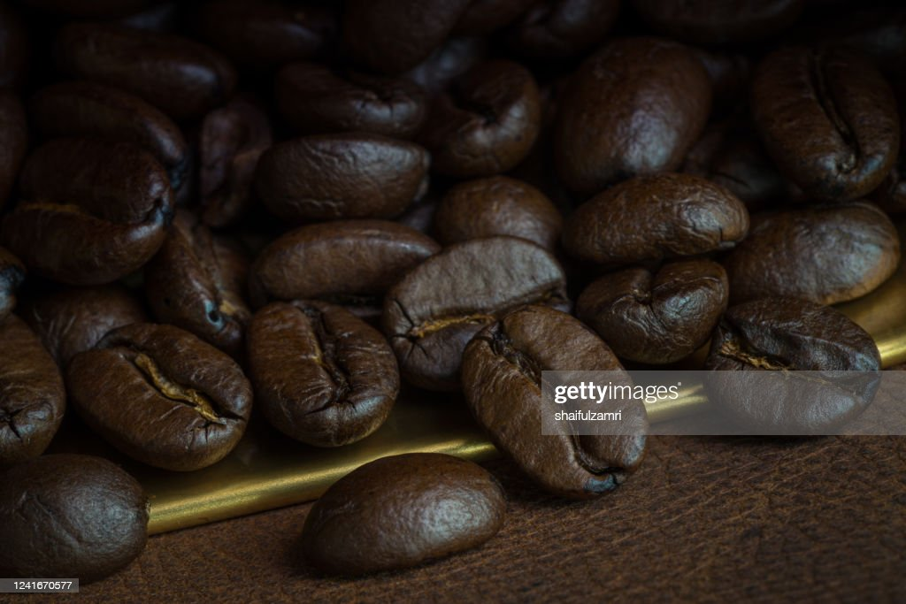 Roasted coffee beans over leather : Stock Photo