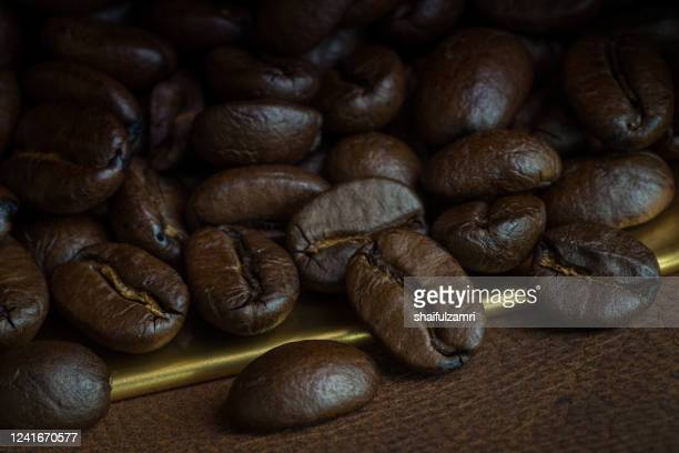 roasted coffee beans over leather - shaifulzamri stock pictures, royalty-free photos & images