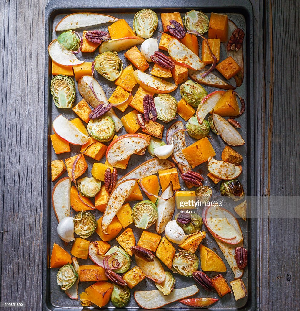 Roasted cut vegetables and fruit on a baking sheet. : Stock Photo