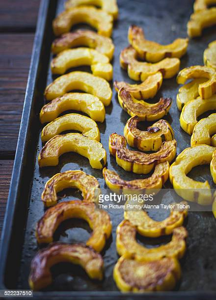 Roasted delicata squash slices on a pan.