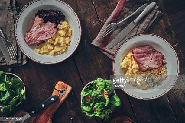 geroosterde ham hock geserveerd met zuurkool en aardappelpuree - zuurkool stockfoto's en -beelden