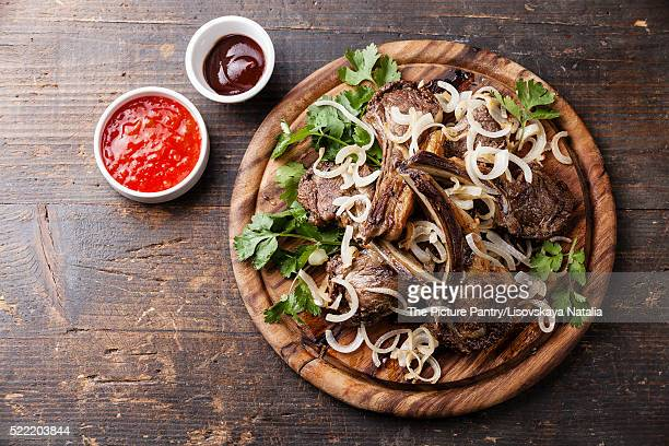Roasted lamb ribs with onion and sauce on dark wooden background