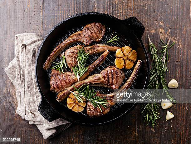 Roasted lamb ribs with rosemary and garlic on grill pan on dark