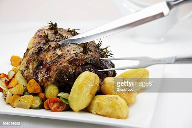 roasted leg of lamb being carved - carving knife stock pictures, royalty-free photos & images