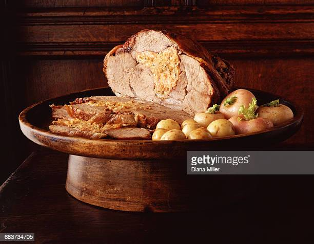 Roasted leg of lamb, de-boned and stuffed with new potatoes on vintage wooden serving tray