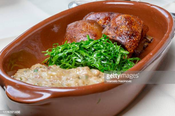 roasted piglet with cabbage mineira and tutu - marcelo nacinovic stock pictures, royalty-free photos & images
