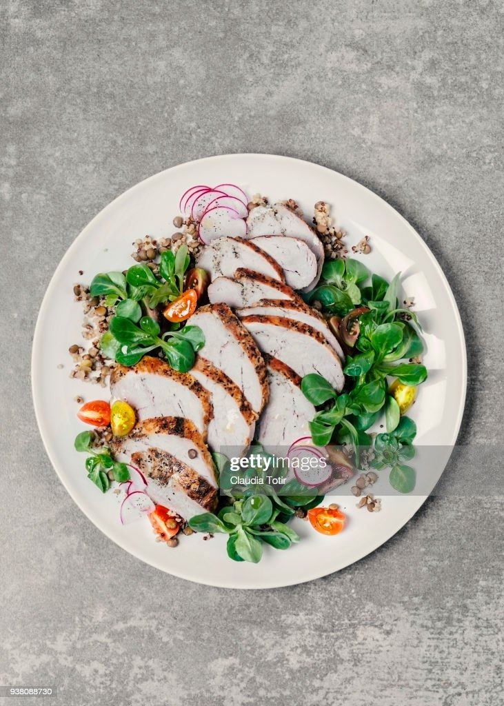 Roasted pork with lentils and fresh salad : Stock Photo