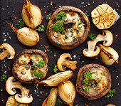 Roasted portobello mushrooms stuffed with cheese and herbs on a black iron  background, top view.