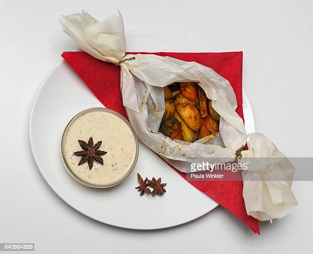 Roasted potatoes and root vegetables by sauce in plate