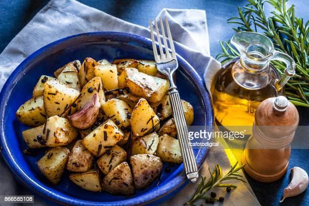 木製キッチン テーブルの上の青い皿ポテトのロースト - ローストポテト ストックフォトと画像