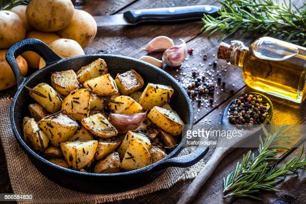 roasted potatoes on wooden kitchen table - cooking pan stock pictures, royalty-free photos & images